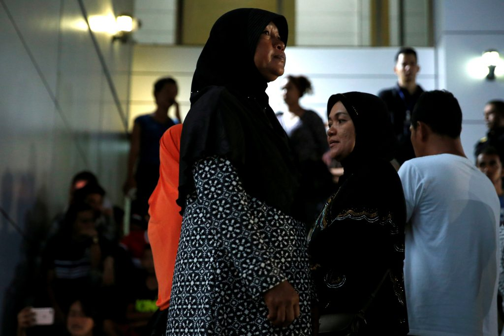 Relatives of victims of human trafficking wait for the sentence after an army general, two provincial politicians and police officers were among the 46 people held guilty in a court in Bangkok