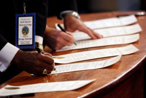 North Carolina's Electoral College representatives sign the Certificates of Vote after affirming their votes, all for U.S. President-elect Donald Trump, at a ceremony in the State Capitol building in Raleigh, North Carolina, U.S., December 19, 2016. REUTERS/Jonathan Drake - RTX2VPL2