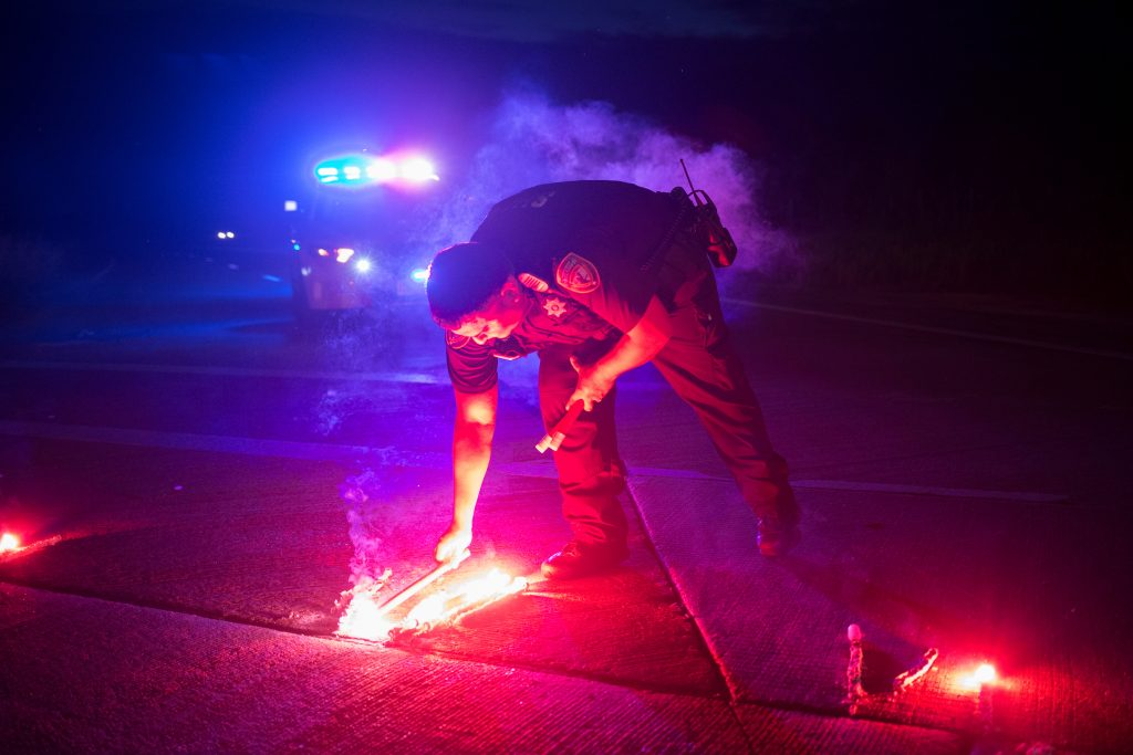 A police officer lays down a safety flare while blocking the road leading to the Arkema SA plant which was hit by floods caused Tropical Storm Harvey near Crosby, Texas, U.S. August 31, 2017. Photo by Adrees Latif/REUTERS