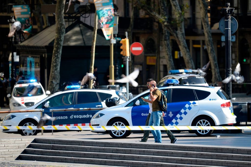 Plain-clothes policemen walk through a cordoned-off area after a van plowed into the crowd, injuring several persons on La Rambla in Barcelona on Aug. 17. Photo by Josep Lago/AFP/Getty Images