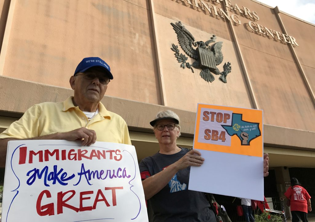 """Protesters against the Texas state law to punish """"sanctuary cities"""" stands outside the U.S. Federal court in San Antonio, Texas. Photo by Jon Herskovitz/Reuters"""