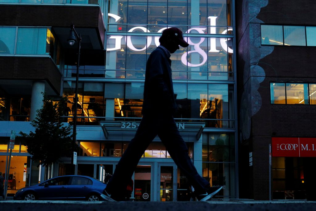 A pedestrian walks past the Google offices in Cambridge, Massachusetts, U.S., June 27, 2017. This logo has been updated and is no longer in use. REUTERS/Brian Snyder - RTS18WDQ