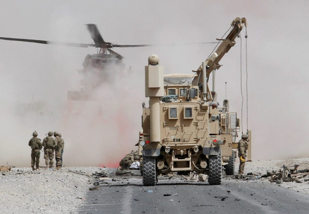 U.S. troops assess the damage to an armoured vehicle of NATO-led military coalition after a suicide attack in Kandahar province