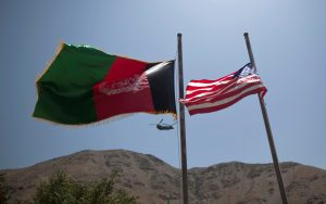 FILE PHOTO - An Afghan flag flutters next to a U.S. flag as a U.S Chinook helicopter flies during a security handover ceremony in Panjshir province