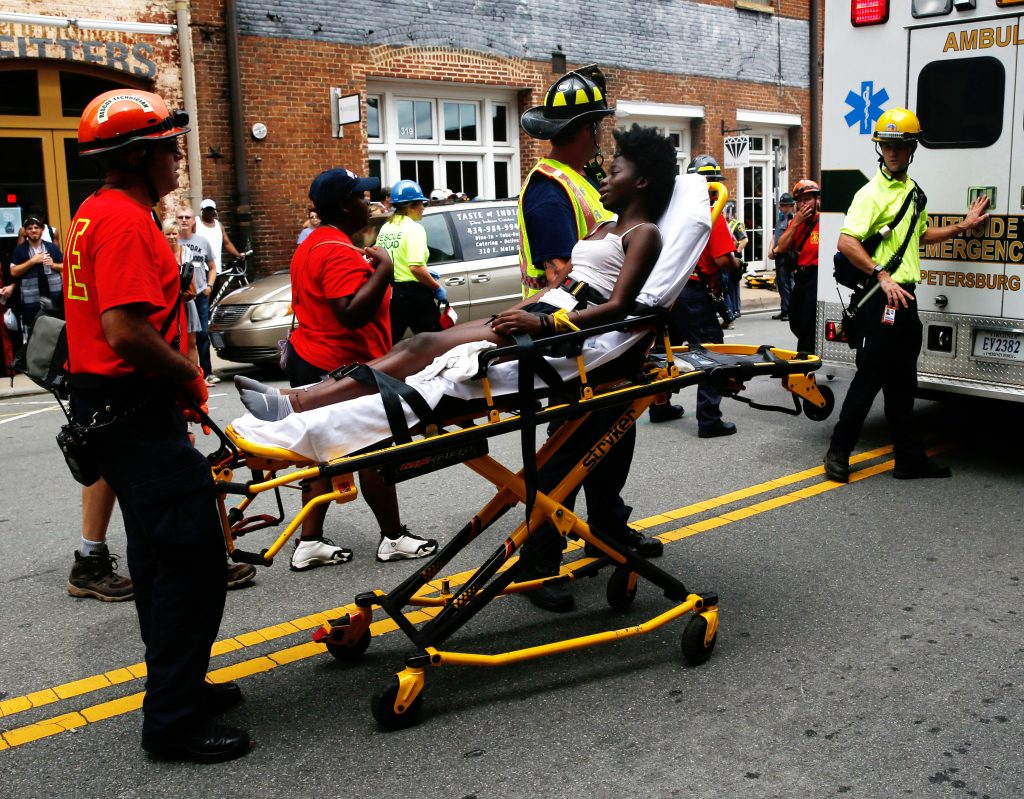 "Rescue workers transport a victim who was injured when a car drove through a group of counter protestors at the ""Unite the Right"" rally Charlottesville"