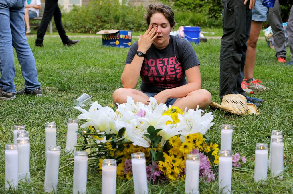 """A local resident of Charlottesville who did not wish to be identified, wipes tears from her eyes at a vigil where 20 candles were burned for the 19 people injured and one killed when a car plowed into a crowd of counter protesters at the """"Unite the Right"""" rally organized by white nationalists in Charlottesville, Virginia, U.S., August 12, 2017. REUTERS/Jim Bourg - RTS1BK09"""