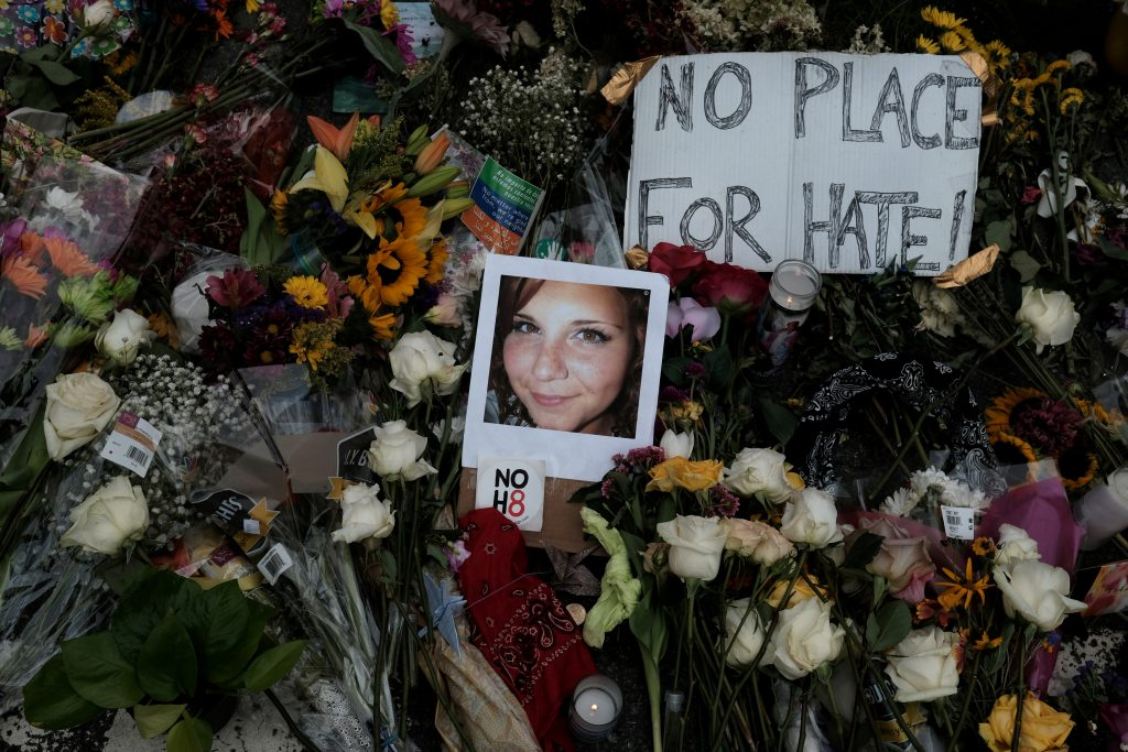 """FILE PHOTO: A photograph of Charlottesville victim Heather Heyer is seen amongst flowers left at the scene of the car attack on a group of counter-protesters that took her life during the """"Unite the Right"""" rally as people continue to react to the weekend violence in Charlottesville, Virginia, U.S. August 14, 2017.  REUTERS/Justin Ide/File Photo"""