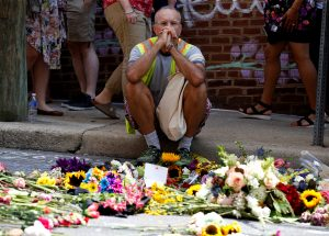 A man looks at flowers placed on the road where Heather Heyer was killed when a suspected white nationalist crashed his car into anti-racist demonstrators in Charlottesville, Virginia, U.S., August 16, 2017.   REUTERS/Joshua Roberts