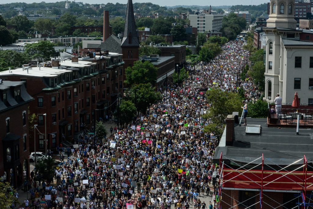 A large crowd of people march towards the Boston Commons to protest…