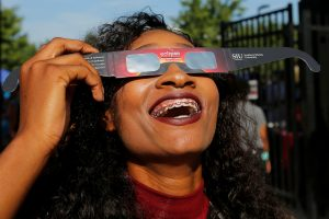 A cheerleader uses solar viewing glasses before the total solar eclipse at Southern Illinois University in Carbondale, Illinois. Photo by Brian Snyder/Reuters