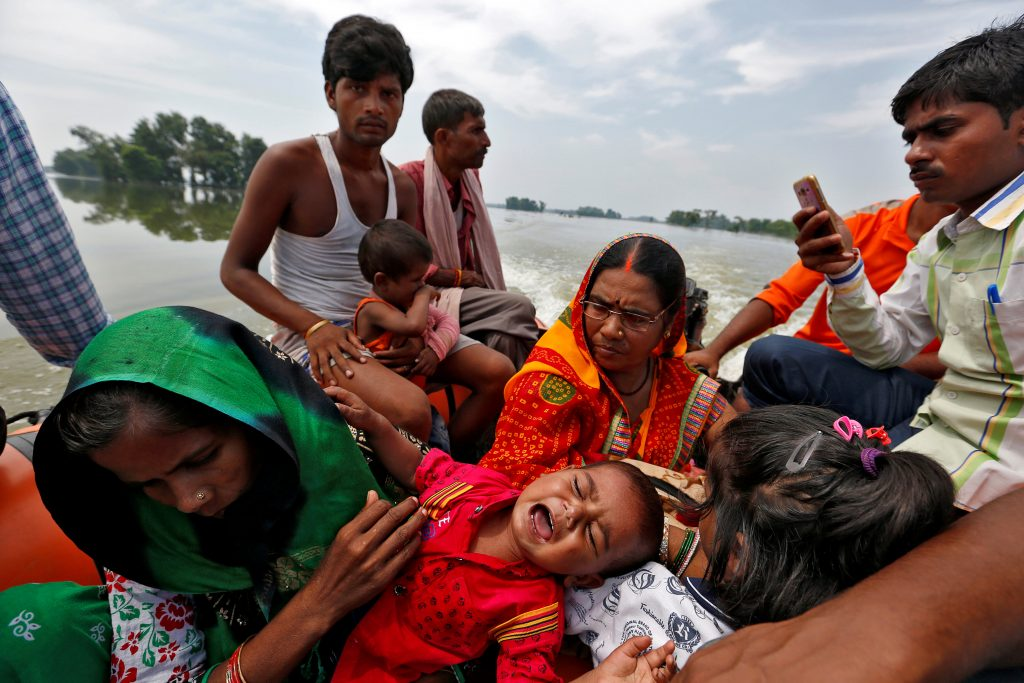 A family is rescued from a flooded village in the eastern state of Bihar, India on Aug. 23. Photo by Cathal McNaughton/Reuters