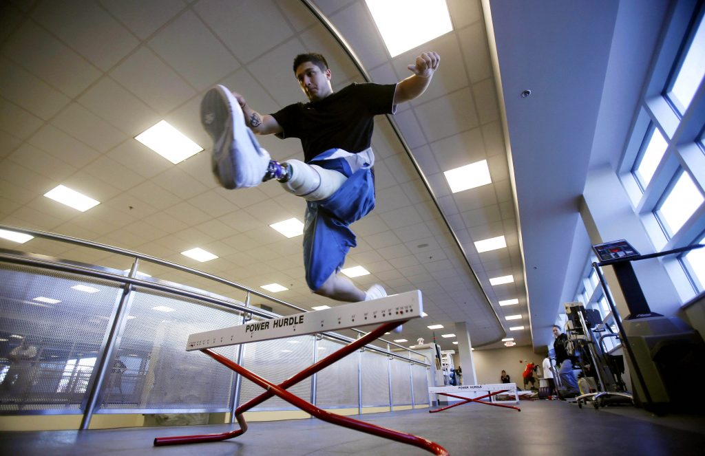 Army Specialist Saul Bosquez leaps over a hurdle using an artificial leg during rehabilitation at the Military Advanced Training Center at Walter Reed Army Medical Center in Washington November 6, 2007. To match story IRAQ-USA/AMPUTEES. REUTERS/Jim Young (UNITED STATES) - RTX1CG