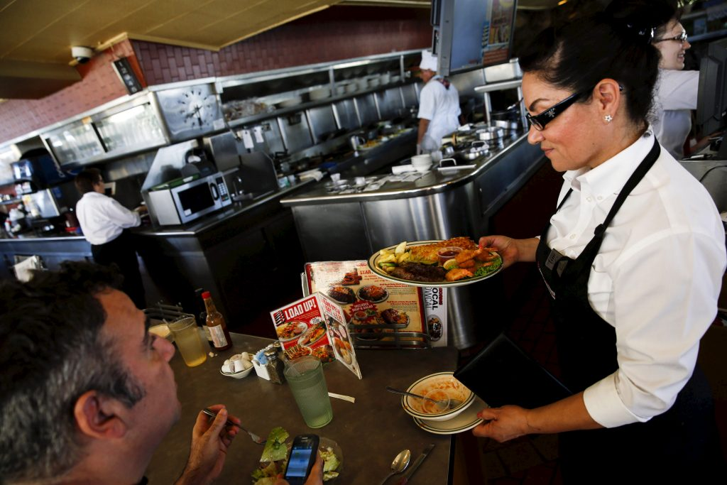 "A waitress serves a steak and fried shrimp combo plate to a customer at Norms Diner on La Cienega Boulevard in Los Angeles, California May 20, 2015. The diner, celebrated as a classic example of mid-20th century Space Age-style Googie architecture, was granted historic monument status by city officials on Wednesday, protecting it from the threat of demolition. The Los Angeles City Council voted unanimously with three people absent to designate the 1956 Norms restaurant as a ""historic-cultural monument,"" citing the need to preserve distinctive buildings of the city. REUTERS/Patrick T. Fallon - RTX1DVSE"