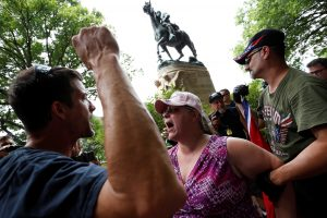 A woman who supports Confederate symbols and monuments is held by her husband (R) as she exchanges words with a counter-protester as they wait for members of the Ku Klux Klan to rally in support of Confederate monuments, such as the statue of General Stonewall Jackson behind them, in Charlottesville, Virginia, on July 8, 2017. Photo by Jonathan Ernst/Reuters