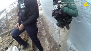 A still image captured from police body camera video appears to show two Baltimore police officers look on as a colleague places a small plastic bag in a trash-strewn yard (not shown), according to the Maryland Office of the Public Defender in this image released in Baltimore on July 19, 2017.    Photo courtesy of Baltimore Police Department via Reuters