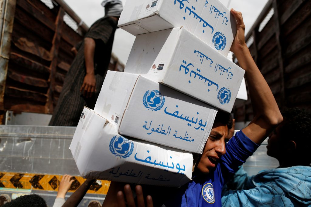 A volunteer carries hygiene kits provided by UNICEF in Sanaa, Yemen. Aid groups also are distributing chlorine tablets to clean water sources. Photo by Khaled Abdullah/Reuters