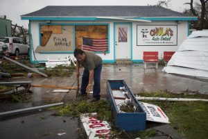 Business owner and resident clears debris from outside his shop which was hit by Hurricane Harvey in Rockport, Texas