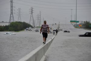 A stranded motorist escapes floodwaters on Interstate 225 after Hurricane Harvey inundated the Texas Gulf coast with rain causing mass flooding