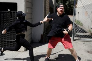 A photographer is attacked by a masked demonstrator in Martin Luther King Jr. Civic Center Park during a cancelled No Marxism in America rally and counter-protest in Berkeley, California, on Aug. 27. Photo by Stephen Lam/Reuters