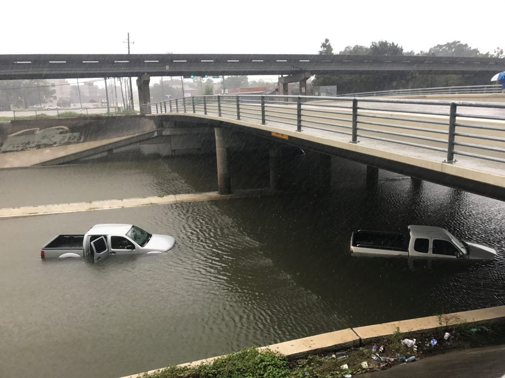 Vehicles sits half submerged in flood waters under a bridge in the aftermath of Hurricane Harvey in Houston, Texas, U.S., August 27, 2017.  Picture taken August 27, 2017. Photo by Ernest Scheyder/REUTERS