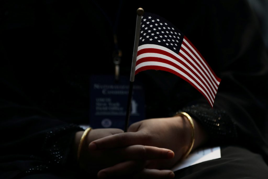 An immigrant woman holds a U.S. flag during a U.S. Citizenship and Immigration Services Naturalization ceremony in the New York Public Library in New York, U.S., June 30, 2017. REUTERS/Shannon Stapleton TPX IMAGES OF THE DAY - RTS19AZZ