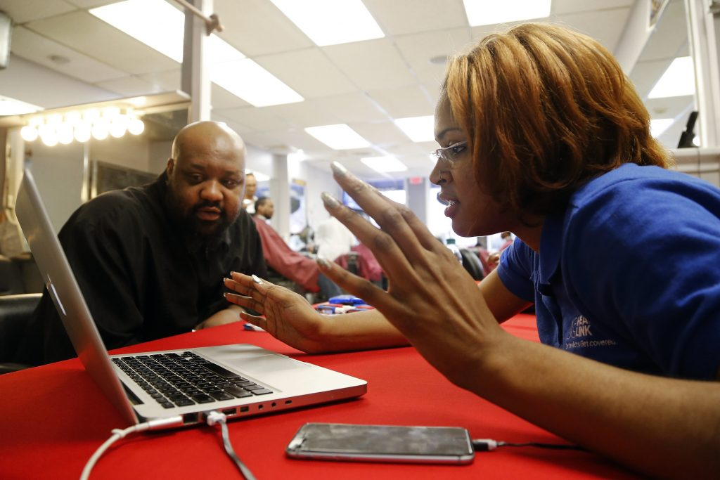 Karima Williams (R) of DC Health Link assists barber Cornel Henry (L) with health insurance information during an event for National African American Enrollment Week of Action, an initiative of the White House and U.S. Department of Health and Human Services, at Best Cuts Barbershop in Washington January 24, 2015. The Obama administration say they hope to have 9.1 million people enrolled in 2015 coverage under the Affordable Care Act nationwide by the end of the year. REUTERS/Jonathan Ernst (UNITED STATES - Tags: POLITICS HEALTH) - GM1EB1P09F601