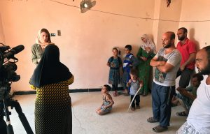 A Syrian family watches as Gayle Tzemach Lemmon conducts an interview. Photo by Jon Gerberg/PBS NewsHour