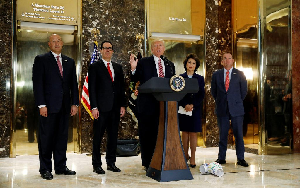 "U.S. President Donald Trump is flanked by (L-R) Director of the National Economic Council Gary Cohn, Treasury Secretary Steven Mnuchin, Secretary of Transportation Elaine Chao and Director of the Office of Management and Budget Mick Mulvaney as he speaks about the violence, injuries and deaths at the ""Unite the Right"" rally in Charlottesville while talking to the media in the lobby of Trump Tower in Manhattan, New York, U.S., August 15, 2017. REUTERS/Kevin Lamarque - RTS1BXQL"