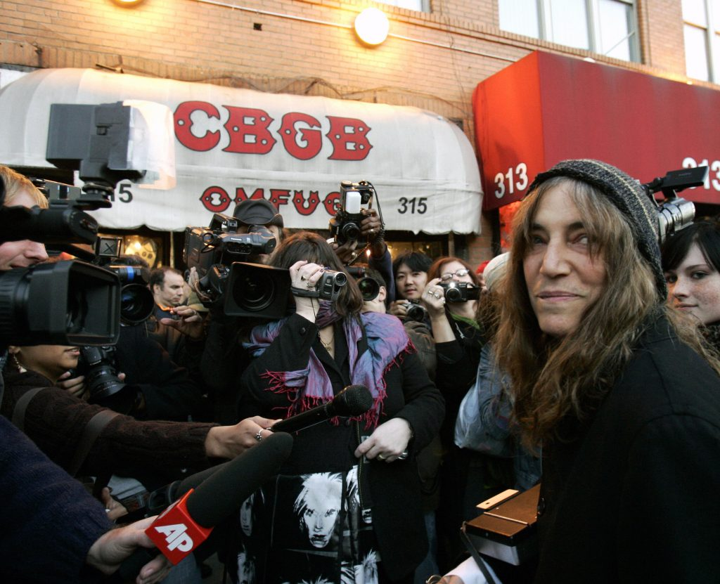 New York, UNITED STATES: Rock star and poet Patti Smith (R) comes outside to take pictures of CBGB, New York's most famous punk bar on its closing night 15 October 2006 after 33 years. Smith was the final performer in the club, that was closed after a homeless advocacy group that owns the property, the Bowery Residents Committee, would not renew CBGB's lease. AFP PHOTO Timothy A. CLARY (Photo credit should read TIMOTHY A. CLARY/AFP/Getty Images)