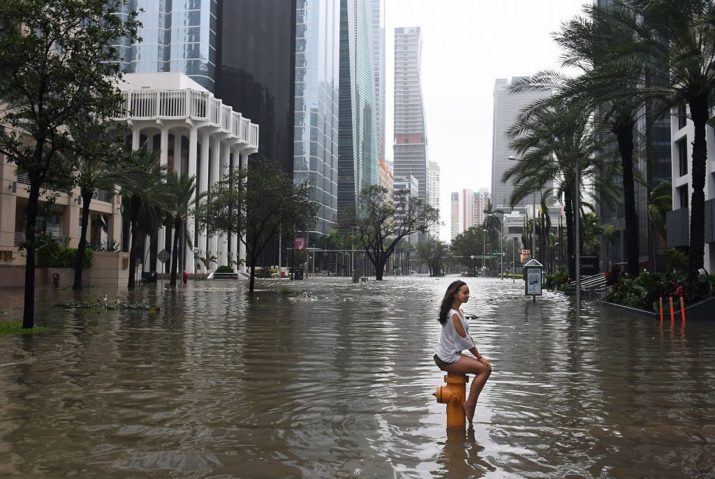 A woman sits atop a fire hydrant on a flooded street in Miami as Hurricane Irma hits Florida on Sept. 10. Photo by Matt McClain/The Washington Post via Getty Images