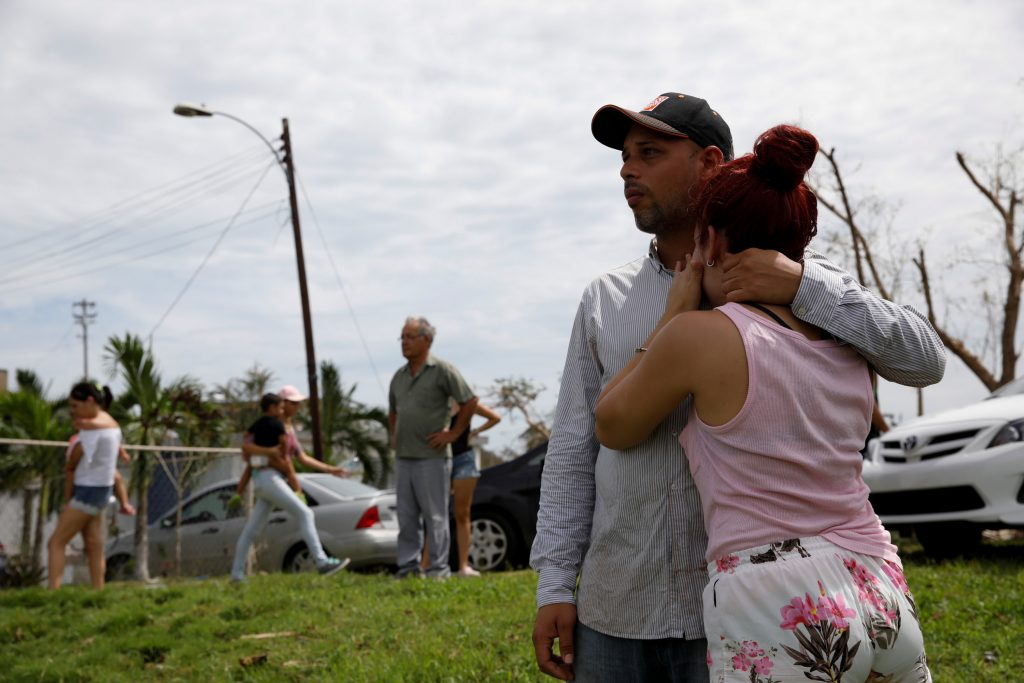 Local residents react while they look at the water flowing over the road at the dam of the Guajataca lake after the area was hit by Hurricane Maria in Guajataca
