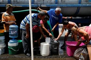 People queue to fill containers with water from a tank truck at an area hit by Hurricane Maria in Canovanas