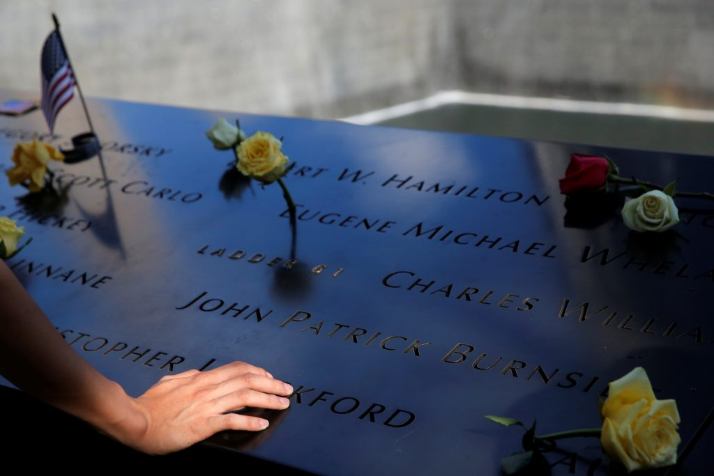 A person touches the south reflecting pool at the National September 11 Memorial and Museum on the 15th anniversary of the 9/11 attacks in Manhattan, New York, U.S.
