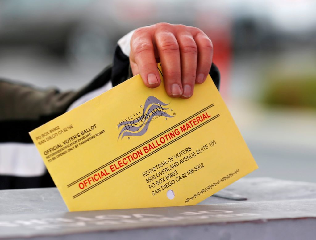 File photo of a poll worker placing a mail-in ballot into a voting box as voters drop off their ballot in the U.S. presidential primary election in San Diego