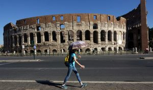 A woman walks past the ancient Colosseum, downtown Rome