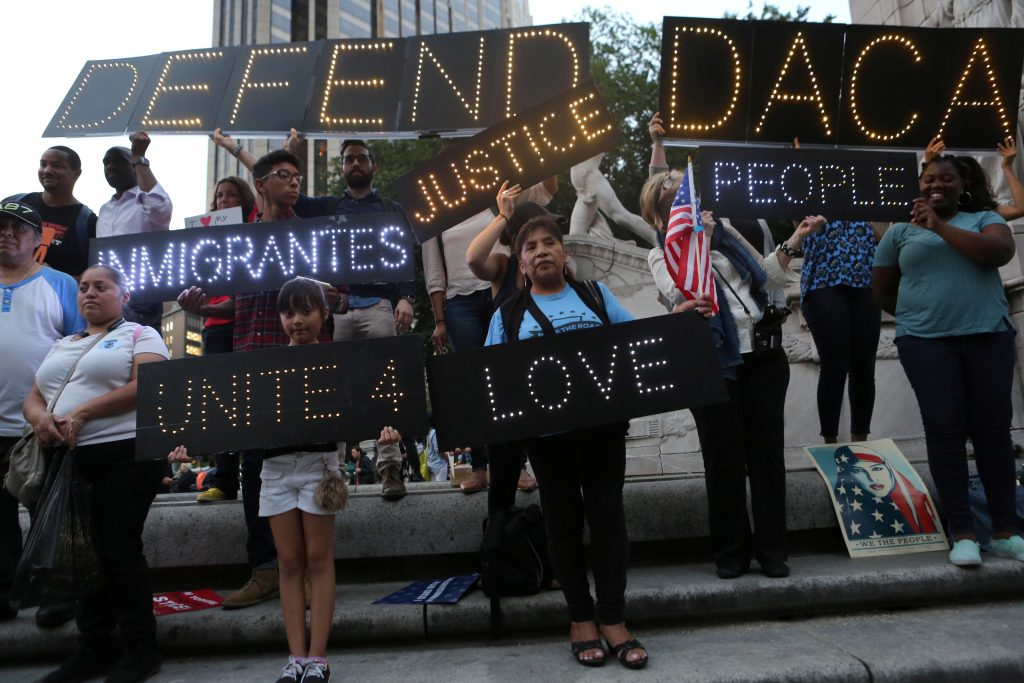 People hold signs against U.S. President Donald Trump's proposed end of the DACA program that protects immigrant children ...