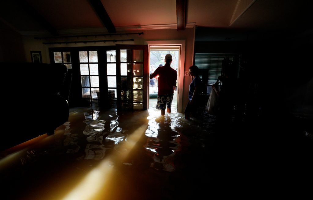 A family that wanted to remain anonymous moves belongings from their home flooded by Harvey in Houston