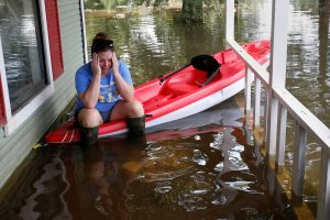 A woman sits on a kayak that is floating on her friend's porch as the house is cleaned of possessions after Tropical Storm Harvey in Orange, Texas, U.S., September 1, 2017. REUTERS/Carlo Allegri - RC15E1538780