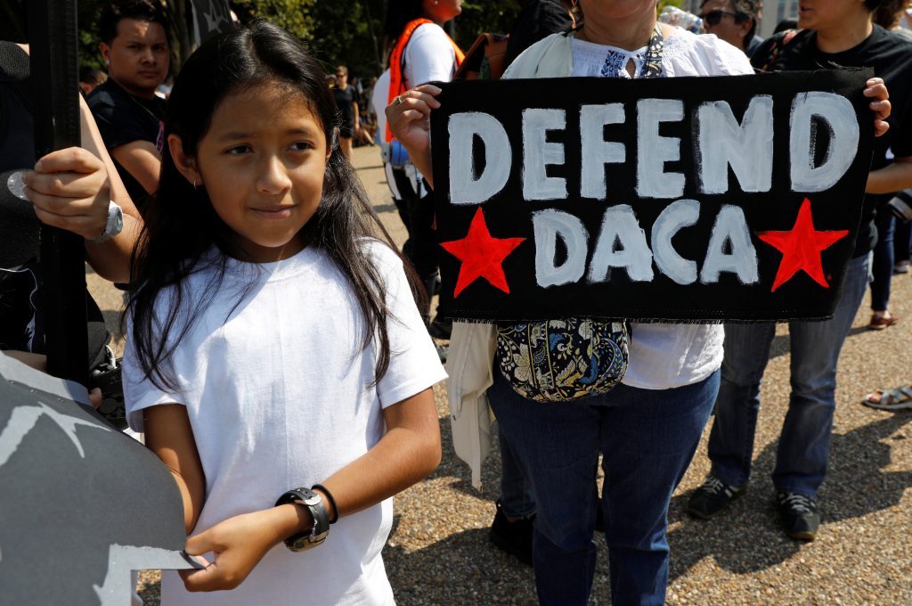 Demonstrators hold signs during a protest in front of the White House after the Trump administration today scrapped the Deferred Action for Childhood Arrivals (DACA), a program that protects from deportation almost 800,000 young men and women who were brought into the U.S. illegally as children, in Washington, U.S., September 5, 2017. REUTERS/Kevin Lamarque - RC12174D8090
