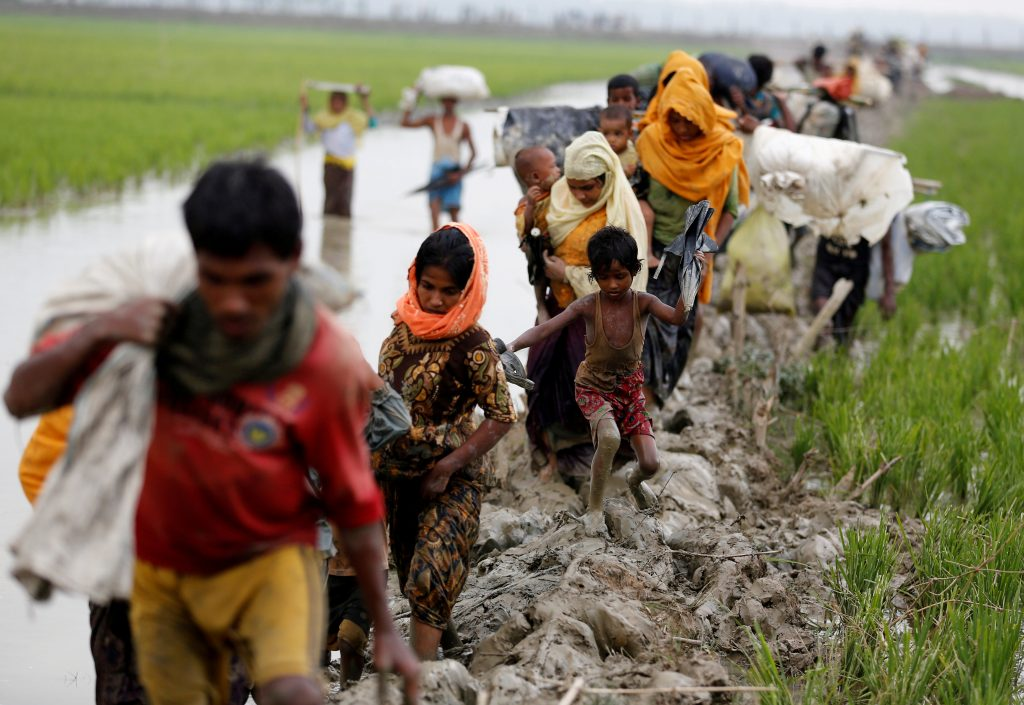 Rohingya refugees walk on a muddy path after crossing the Banglades…