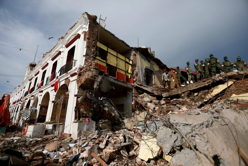 Soldiers remove the debris of a house destroyed in an earthquake that struck off the southern coast of Mexico late on Thursday, in Juchitan