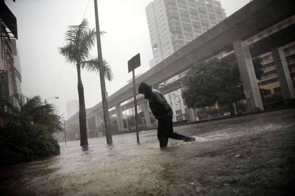 A local resident walks across a flooded street in downtown Miami as Hurricane Irma arrives at south Florida