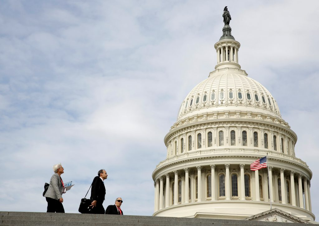 People pass by the U.S. Capitol in Washington, U.S., September 12, 2017. REUTERS/Joshua Roberts - RC184AD807E0