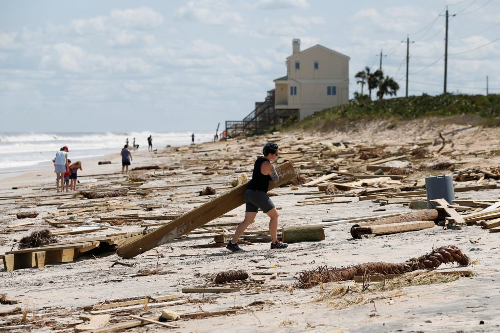 A woman clears debris from the beach after Hurricane Irma passed the area in Ponte Vedra Beach, Florida. Photo by Chris Wattie/Reuters