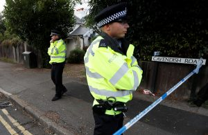 Police officers stand behind cordon tape near a property that was searched after an explosion on a London Underground train, in Sunbury-on-Thames