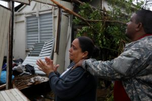 A woman reacts while she looks at the damages in the house of her mother after the area was hit by Hurricane Maria in Guayama
