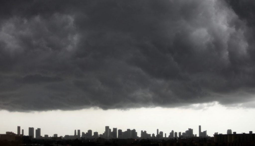 Dark clouds pass over downtown Miami, Florida August 15, 2010. An area of low pressure over southwest Georgia could move southward into Gulf of Mexico waters by early Monday and has a medium chance of becoming a tropical cyclone in the next 48 hours, the National Hurricane Center said on Sunday. The low pressure area was the remnant of Tropical Depression Five which dissipated on Wednesday in the Gulf. The U.S. Gulf of Mexico is home to about 30 percent of U.S. oil production, 11 percent of natural gas production, and more than 43 percent of U.S. refinery capacity. REUTERS/Carlos Barria (UNITED STATES - Tags: ENVIRONMENT IMAGES OF THE DAY) - GM1E68G0FIJ01