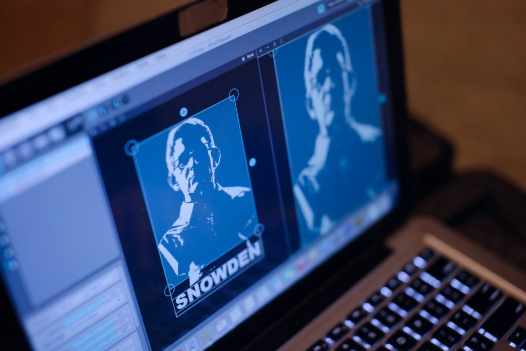 Members of The Illuminator create a projection of Edward Snowden for a Brooklyn Park. Photo courtesy of Emily Andersen/The Illuminator