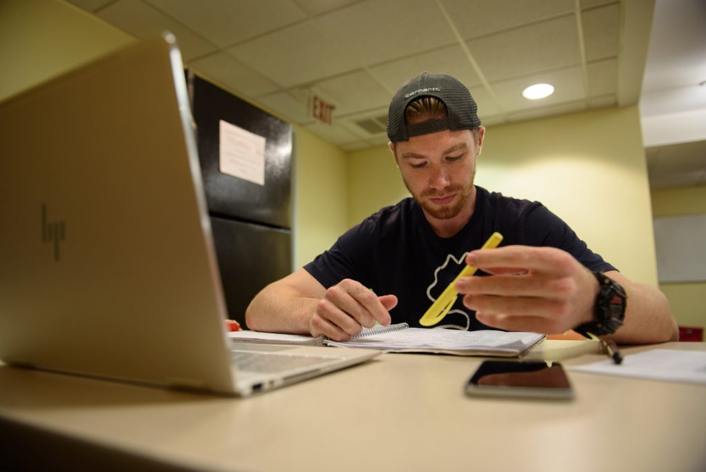 "Josh Caouette, a graduate student at Simmons College, crams for a test. Caouette is resigned to the cost of his degree. ""If it's helping others, that's fine by me. I mean, I have to do it either way."" Photo: Kate Flock for The Hechinger Report"