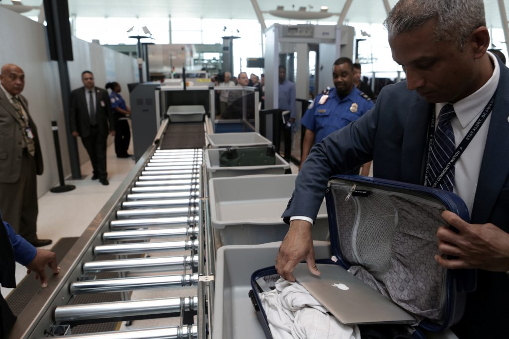 A TSA official removes a laptop from a bag for scanning using the Transport Security Administration's new Automated Screening Lane technology at Terminal 4 of JFK airport in New York City, U.S., May 17, 2017. REUTERS/Joe Penney - RC1E38689C60